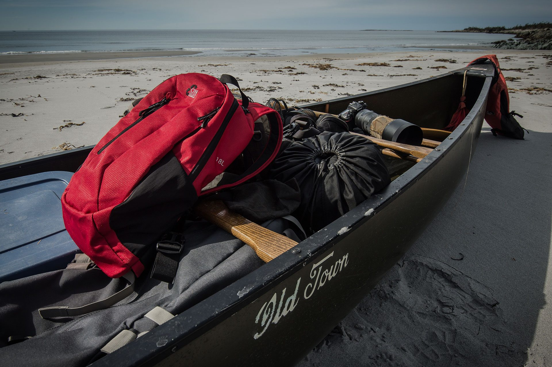 backpack on canoe at beach